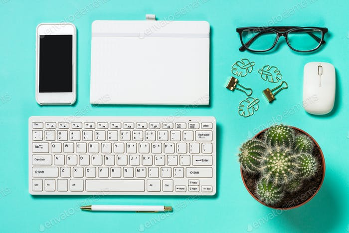 Office workplace with keyboard, notepad, succulent and pen