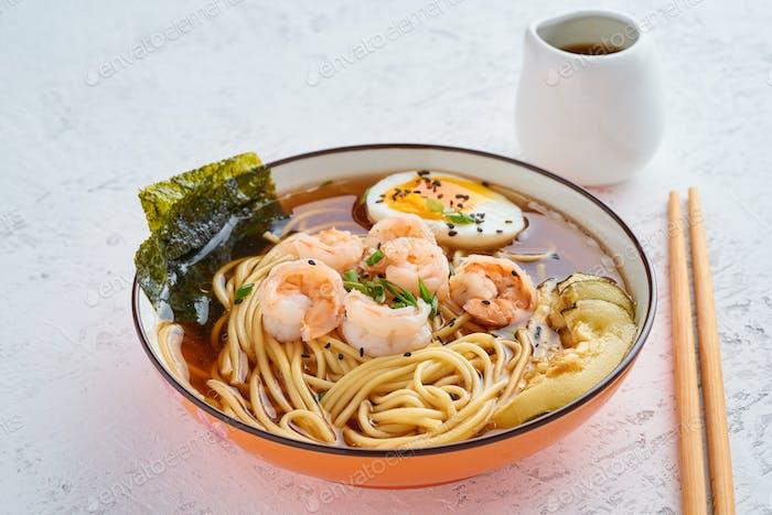 Asiatische Suppe mit Nudeln, Ramen mit Garnelen, Miso-Paste, Sojasauce. Tisch aus weißem Stein, Seitenansicht