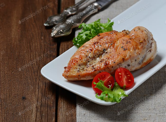 Grilled chicken breasts in white plate