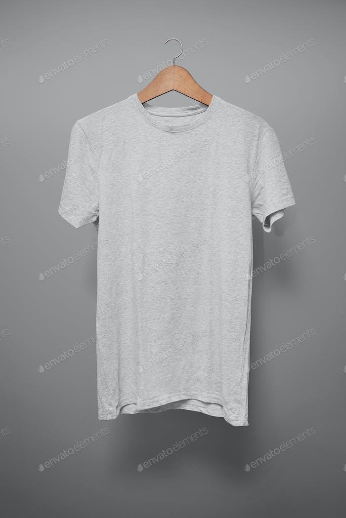 Graues T-Shirt auf einem Kleiderbügel vor grauem Hintergrund