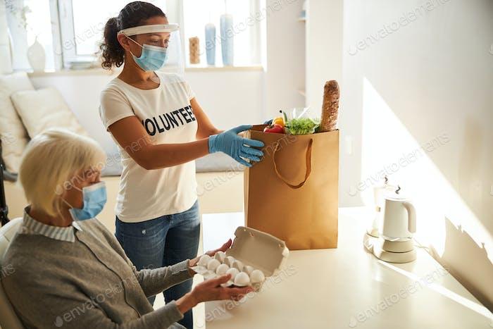 Pensioner having foodstuffs delivered by a volunteer