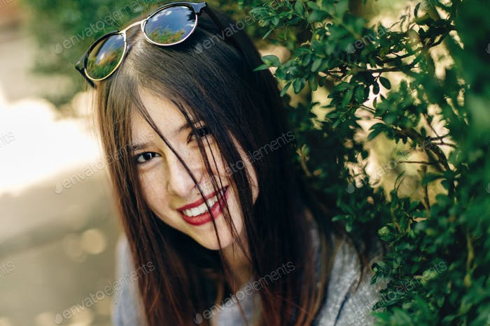 stylish beautiful hipster woman smiling near green leaves in sunny park