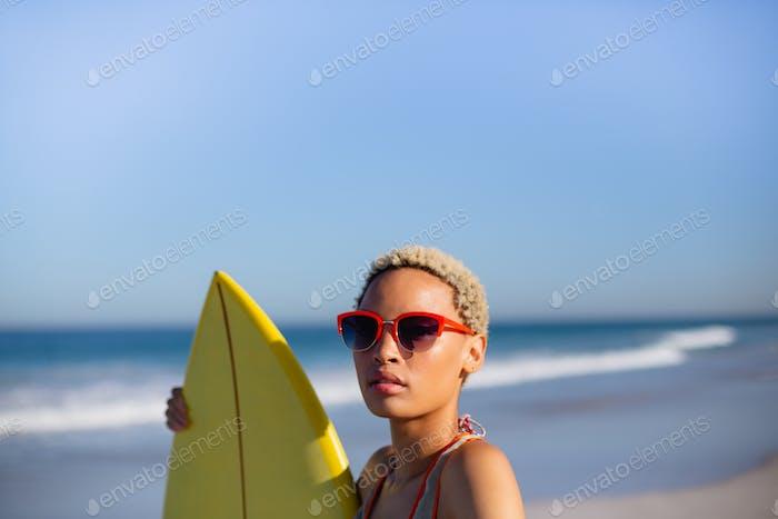 Vorderansicht der schönen Afroamerikanerin stehend mit Surfbrett am Strand in der Sonne