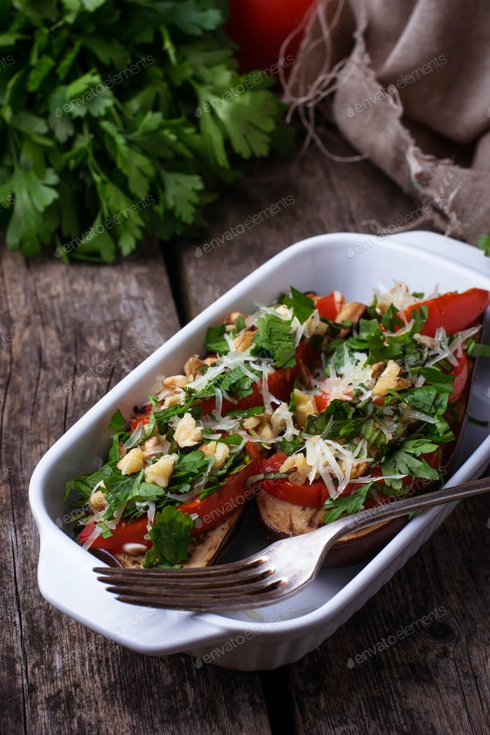 Baked eggplant with cheese, tomato, herbs and nut.