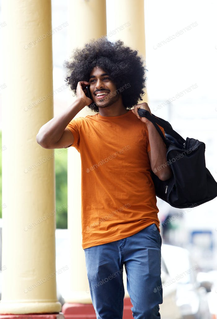 Happy guy walking in town with mobile phone and bag