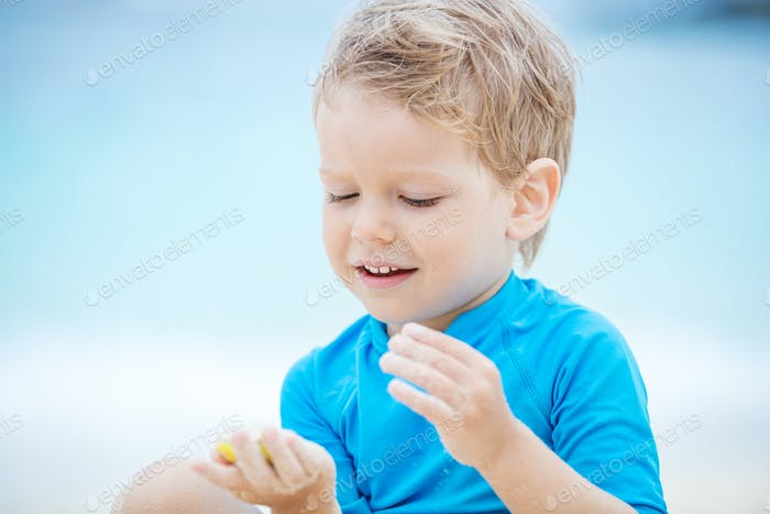 Cute little boy playing on the beach: filling mold shape with sand and smiling