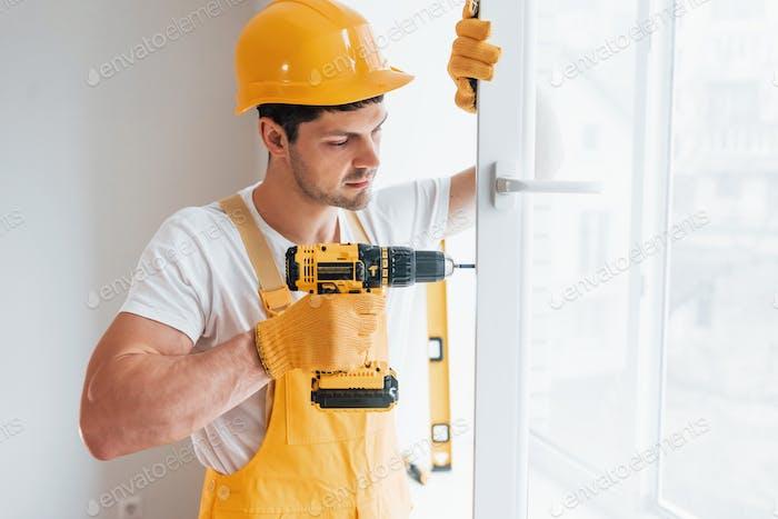 Handwerker in gelber Uniform installiert neues Fenster