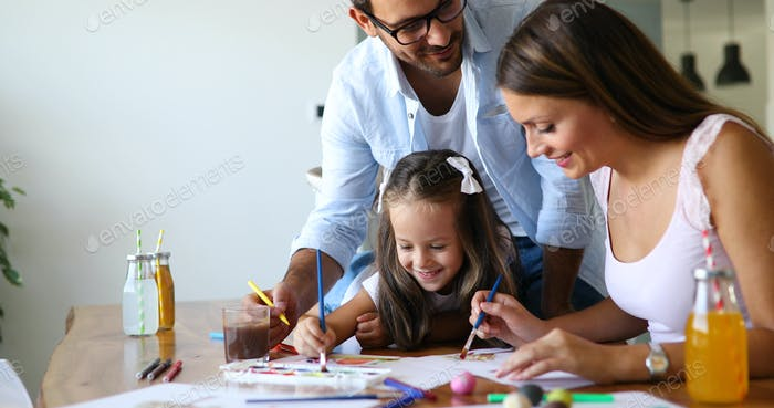 Mother and father drawing together with their child