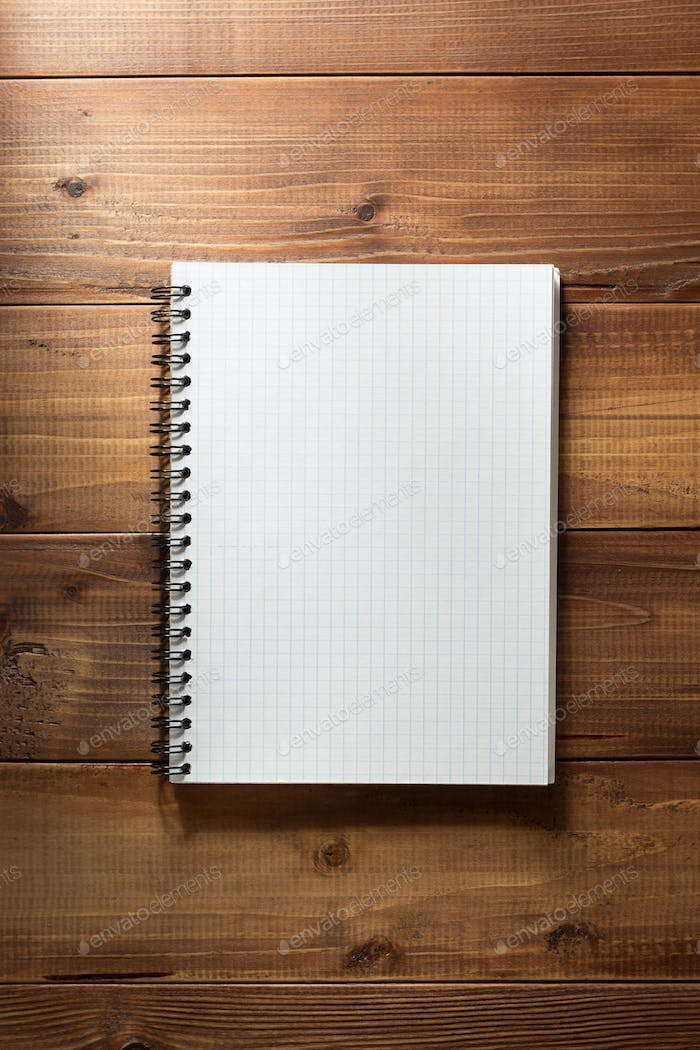 checked notebook on wooden background