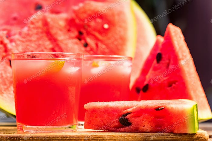 Watermelon slices and juice on wooden table