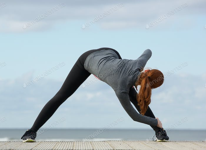 Young woman doing stretching exercises outdoors