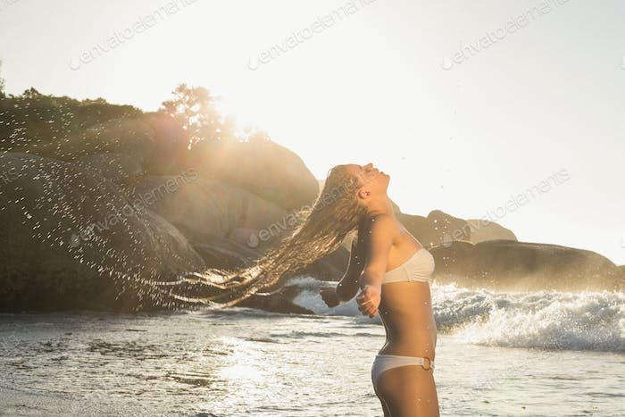 Beautiful blonde in white bikini at the beach tossing wet hair on a sunny day