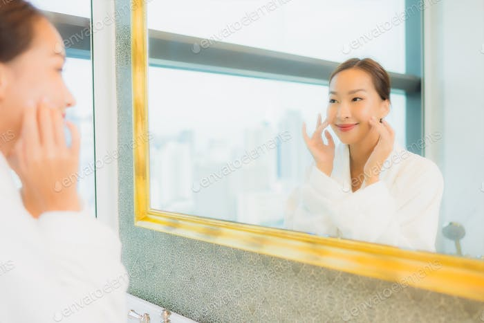 Portrait beautiful young asian woman check up her face on mirror