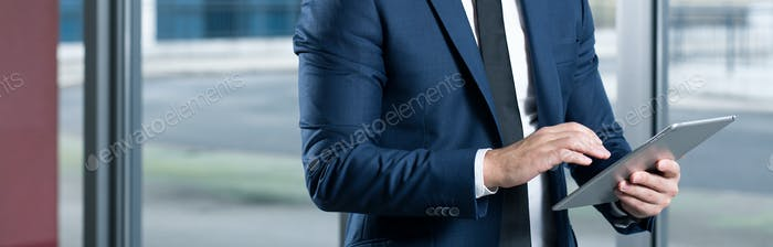 Businessman in suit using tablet