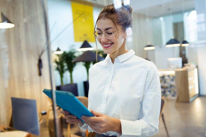 Mujer de negocios joven de moda que trabaja con su tableta digital