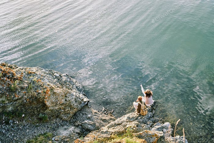 Young female backpacker pointing at far riverbank while sitting by water