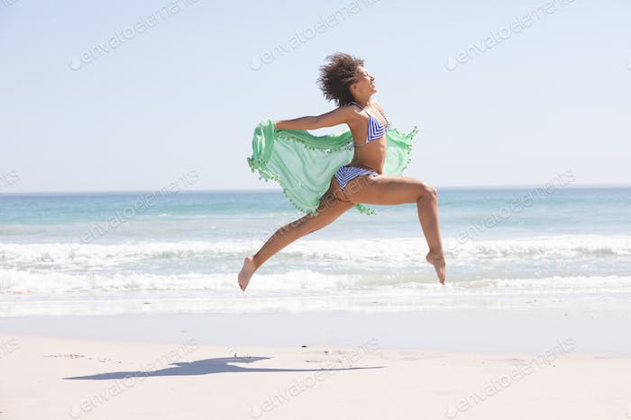 Side view of African american woman in bikini with scarf jumping on the beach