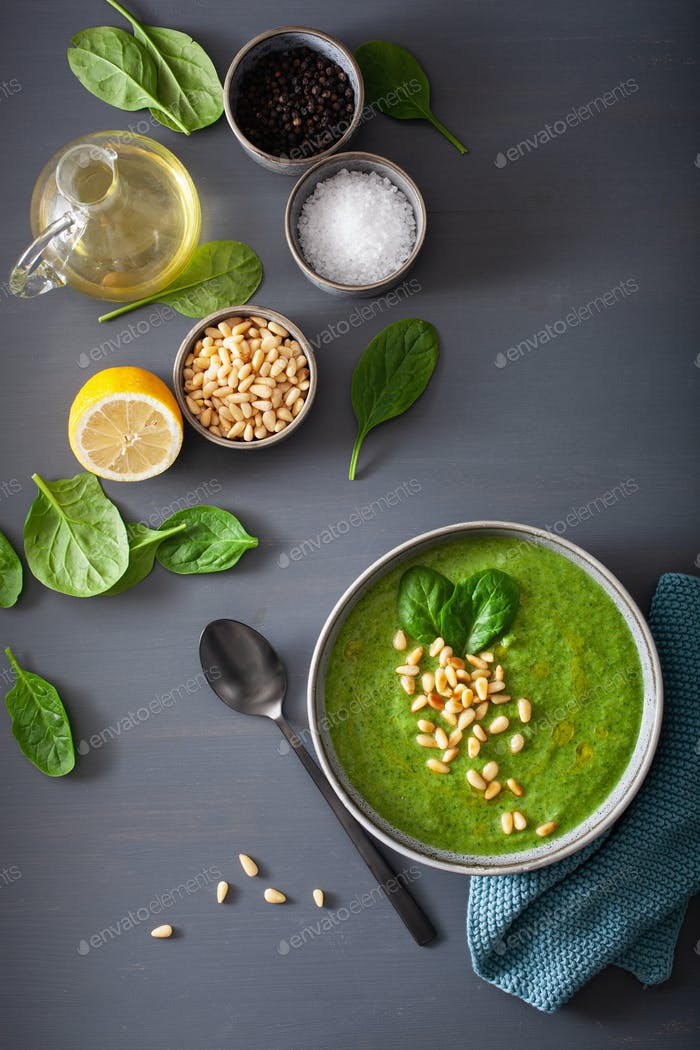 green creamy cauliflower spinach soup on gray background