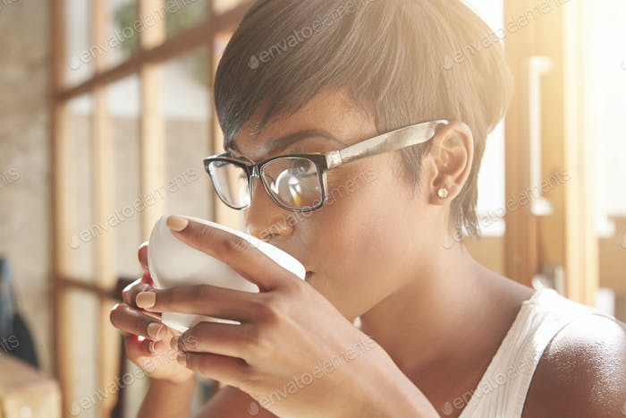 Sideways portrait of young female with chocolate skin. Focused business woman with pixie cut and dia