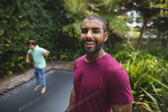 Portrait of smiling father while son jumping on trampoline