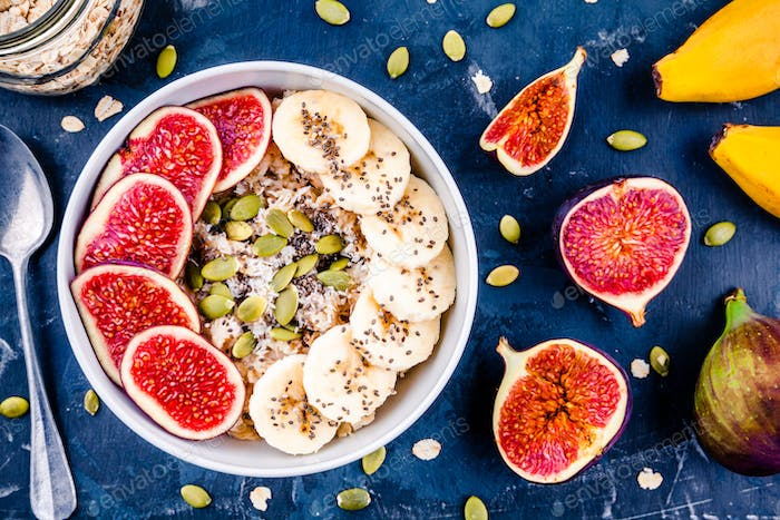 healthy breakfast: oatmeal with fresh figs, bananas, pumpkin seeds, coconut and chia seeds