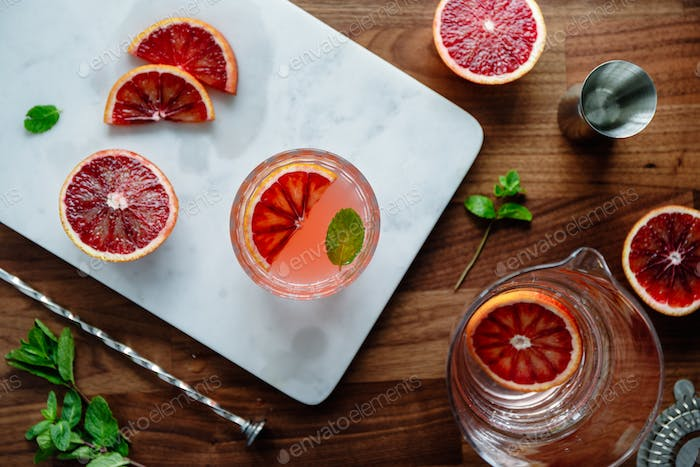 Refreshing cold summer cocktail with blood orange and mint on a marble tray