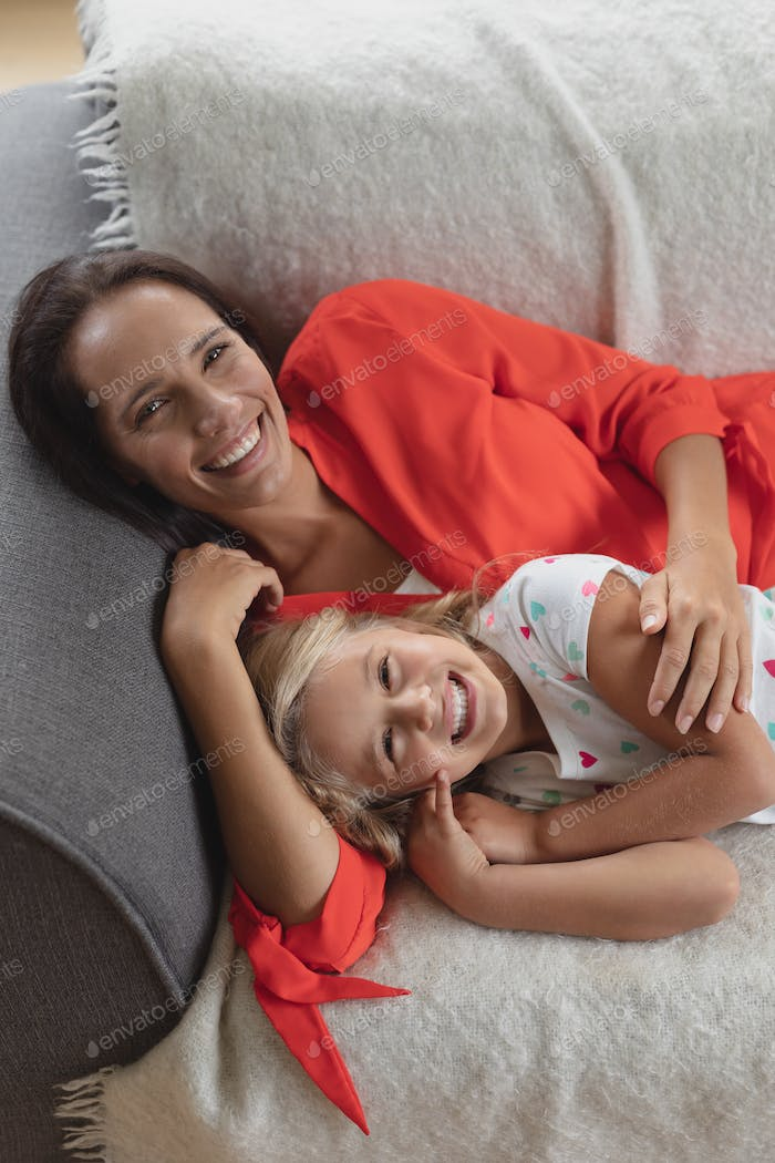 Front view of Caucasian mother and daughter relaxing together on a sofa in living room at home