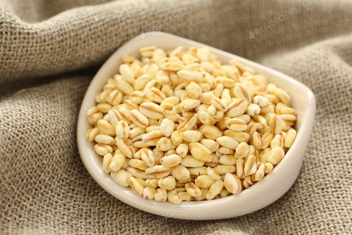 Wheat grains in white ceramic bowl on sackcloth background