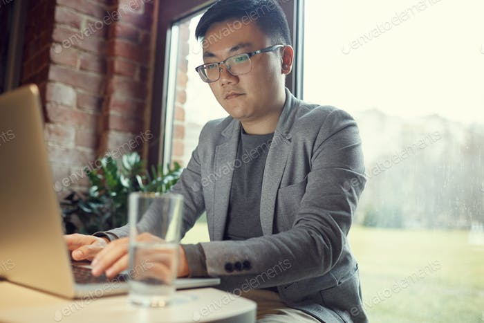 Asian Businessman Looking at Laptop Screen
