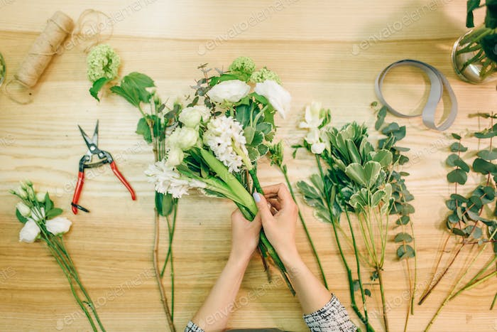 Female florist cuts roses with pruner