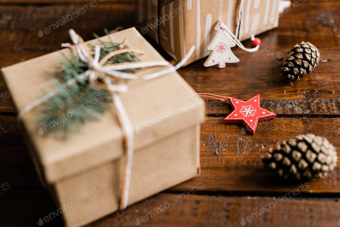 Christmas decorations, pine cones and packed giftbox with conifer on top