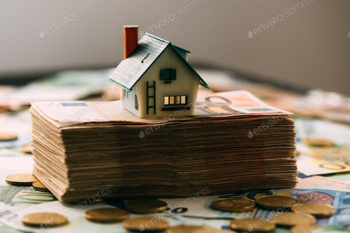 House model on cash stack closeup