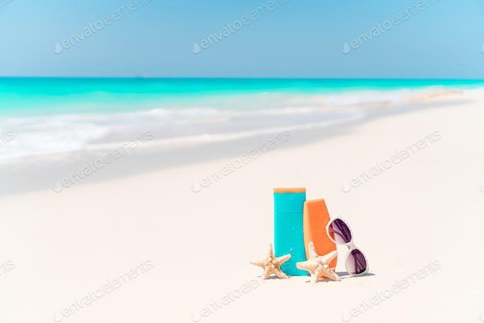 Sonnencreme Flaschen, Brille, Seesterne und Sonnenbrille auf weißem Sand Strand Hintergrund Ozean