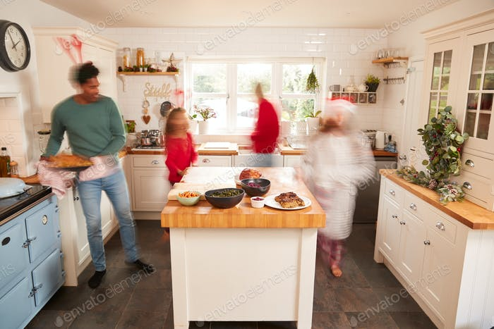 Motion Blur Shot Of Family In Kitchen Helping To Prepare Christmas Meal Together