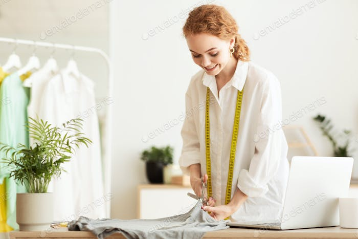 Young dressmaker cutting grey fabric in atelier