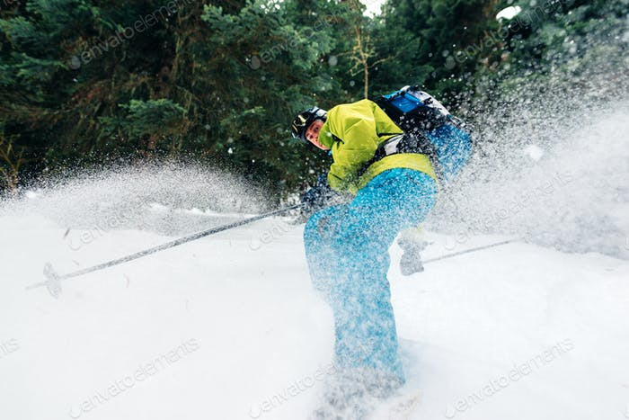 man with special ski equipment is riding and jumping very fast in the mountain forest