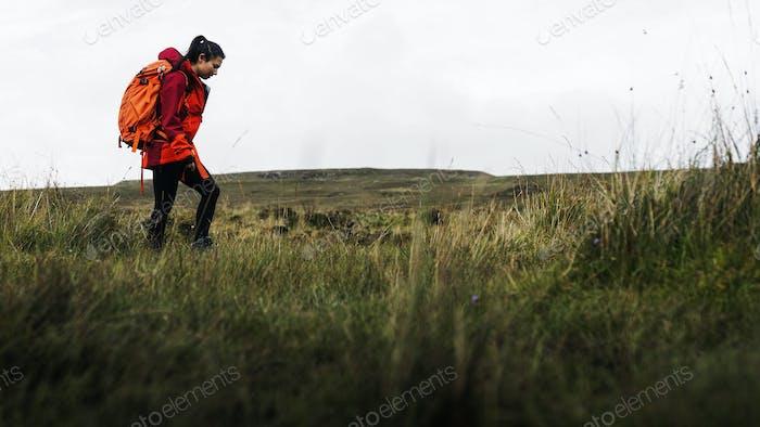 Female hiker walking through a grass field