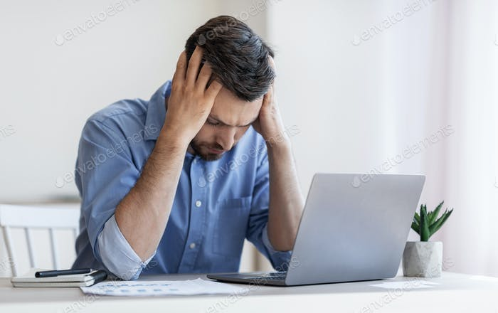 Bankruptcy Concept. Depressed male entrepreneur suffering from business failure, sitting at