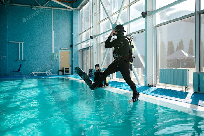 Diver in scuba gear jumps into the pool, diving