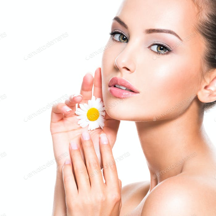 Face of young beautiful woman with singl camomile in hand