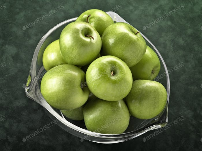 Glass bowl filled with green apples on green background