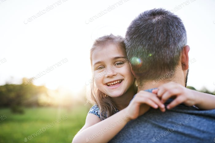 Father holding a small daughter in spring nature at sunset.