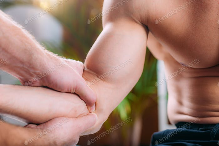 Chiropractic elbow adjustment. Therapist doing manual therapy manipulation technique on an elbow.