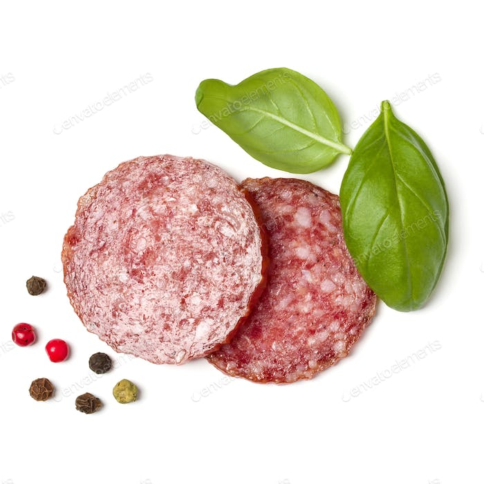 Slices of salami isolated on white background closeup. Sausage and basil leaves top view.