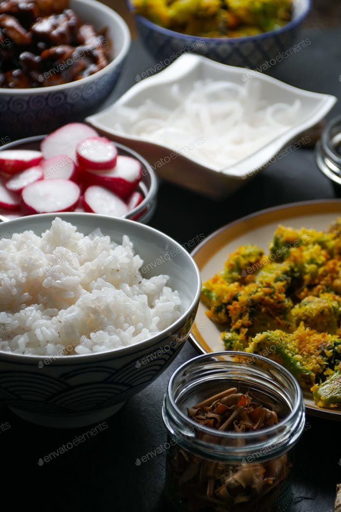 Pieces of teriyaki chicken, rice vermicelli and tempura broccoli on the table.