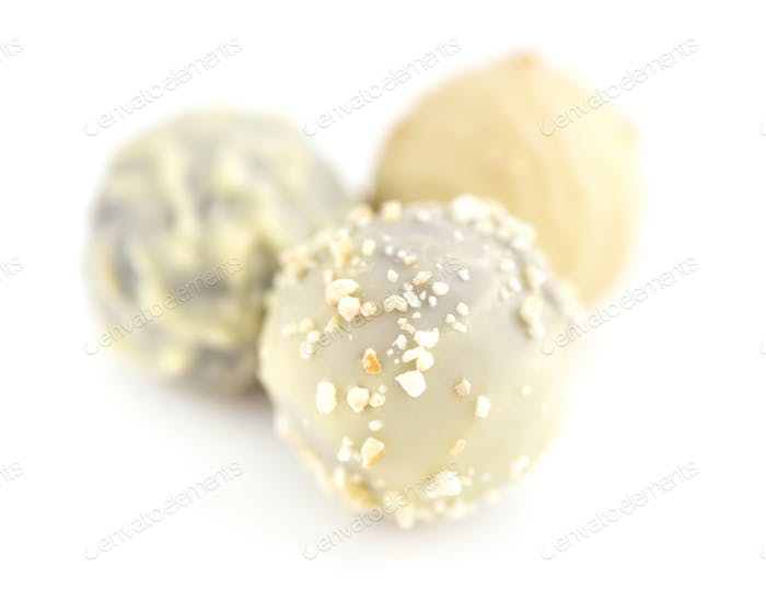 Three candies of white chocolate on white background. Selective