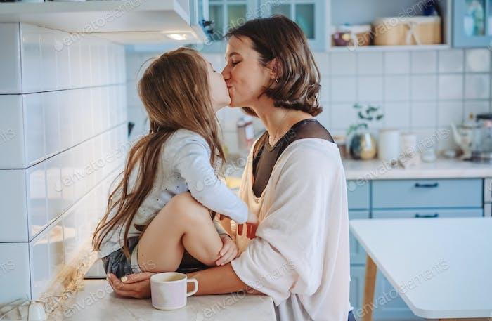 Mama küsst ihre kleine Tochter in die Küche