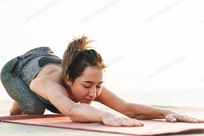 Photo of feminine sportswoman stretching her body on mat while practicing yoga by seaside in morning