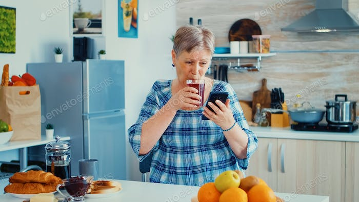 Senior woman using mobile gadget