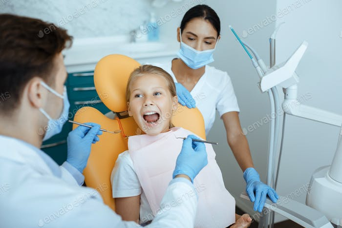 Work of professional doctor and pediatric dentist in modern clinic with equipment